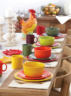 A wooden dining table set with colorful Fiesta plates, bowls & mugs. Shop dining room.