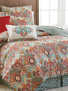 A bed made with a multicolored pattern comforter & matching pillows. Shop bedroom.
