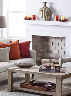 A gray love seat & coffee table in front of a fireplace. There are candles & other decorative touches throughout the room. Shop living room.