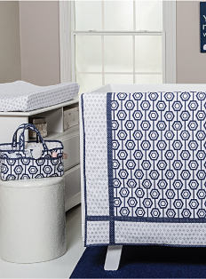 A blue & white baby blanket draped over the side of a white crib. There is a baby bag that matches the blanket. Shop nursery.