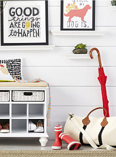 A white shelving unit with a beige seat cushion on top & framed pictures on the wall. Shop mud room.