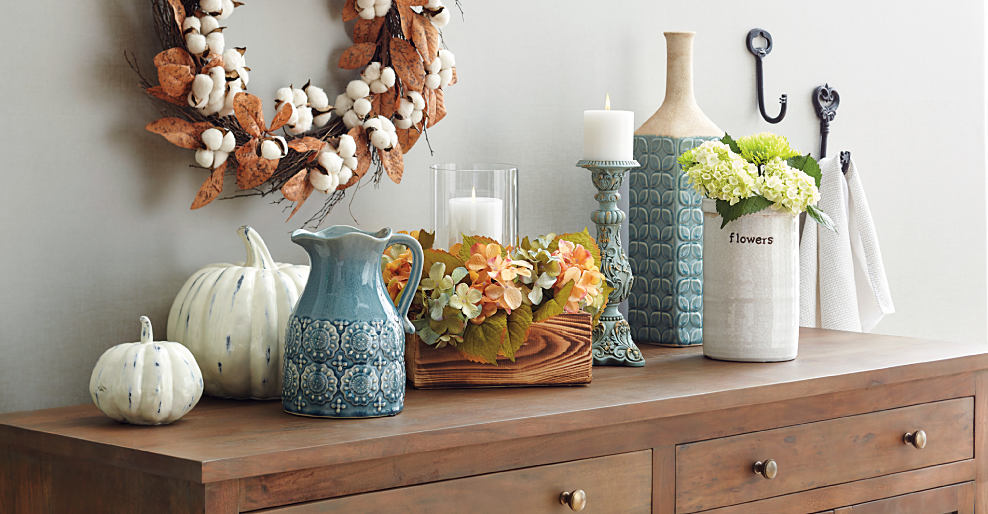A brown wooden dresser with a variety of fall-themed candle holders, vases & white decorative pumpkins on top. There's an autumn harvest wreath hanging on the wall. A harvest of fall decor. Shop now.
