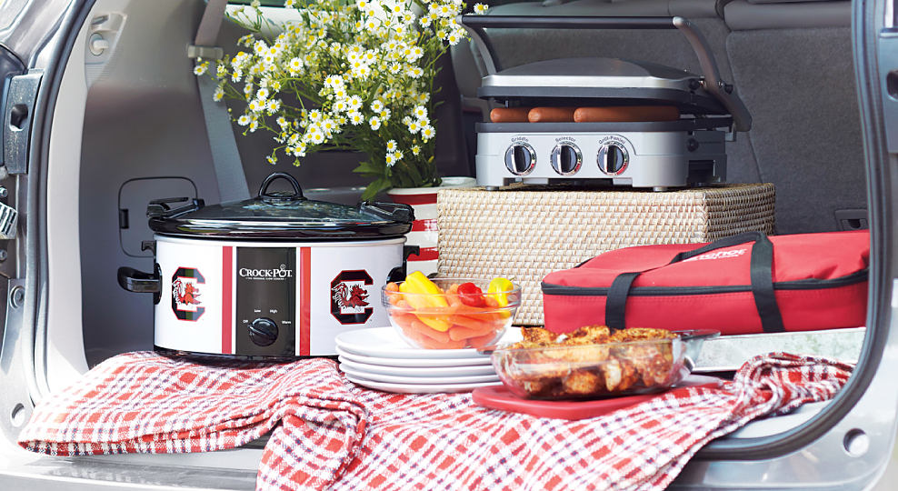 A tailgate of an SUV open with a crockpot, a portable grill, a stack of plates on a picnic blanket. Pregame like a pro. Tailgate with official team gear. Shop now.