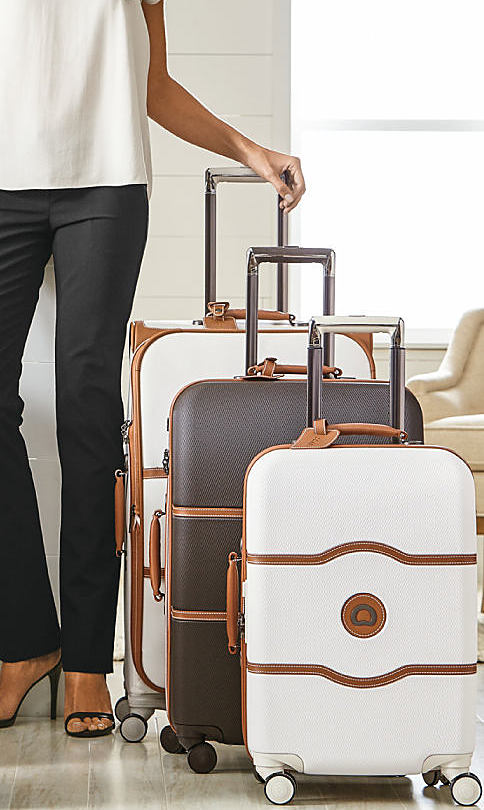 An assortment of white, gray, black & tan wheeled luggage. Shop luggage.