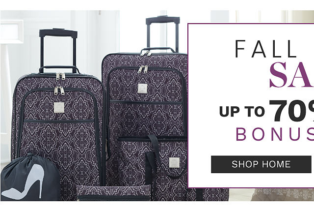 A dark purple & white patterned print 5 piece luggage set. A bed made with a beige & white reversible patterned print quilt & matching pillows. Fall Home Sale Bonus Buys. Shop home.