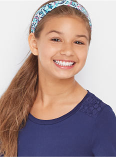 A girl wearing a blue top. Shop girls 7-16.