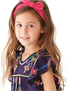 A girl wearing a multi-colored print dress & a fuchsia bow in her hair. Shop girls 4-6X.