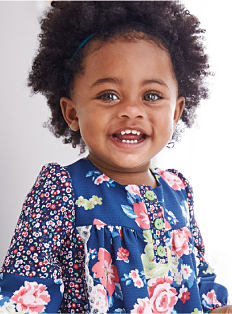 A toddler girl wearing a blue dress with a multi-colored floral print on it. Shop toddler girls.