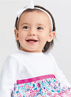 A baby girl wearing a white bow in her hair, a white, pink & multi-colored floral print top. Shop baby girls.