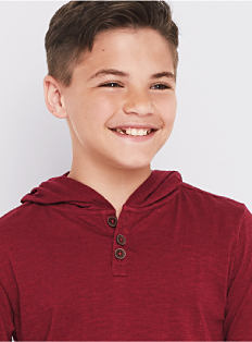 A boy wearing a burgundy short-sleeved hoodie. Shop boys 8-20.