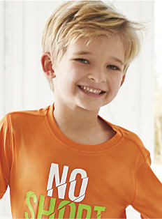 "A boy wearing an orange ""No Short Cuts"" graphic tee, Shop boys 4-7."