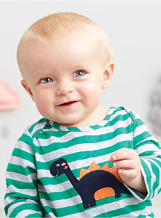 A baby boy wearing a green & white horizontal striped onesie with a dinosaur graphic. Shop baby boys.