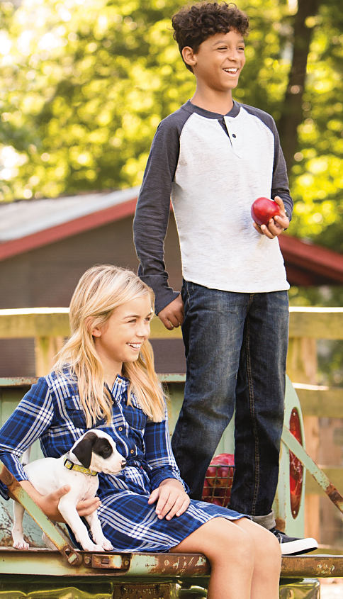 A girl wearing a blue & white plaid dress. A boy wearing a white & gray baseball jersey & blue jeans. Shop True Craft.