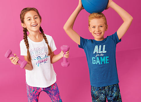 "A girl wearing a ""Girls Rule"" graphic tee & multi-colored shorts standing next to a boy wearing a blue ""All for the Game"" graphic tee & multi-colored shorts. Shop Zelos."