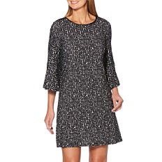 A woman wearing a black & white patterned print long sleeved dress. Shop dresses.