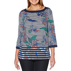 A woman wearing a navy & white horizontal striped long sleeved top with a multi colored floral print & blue jeans. Shop tops.