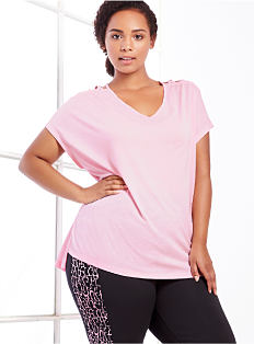 A woman wearing a pink tee & black pants with a multicolored stripe on the side. Shop activewear.