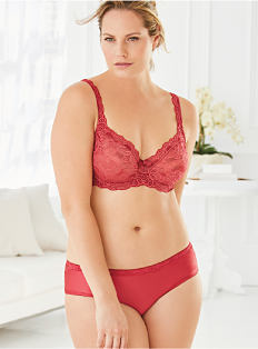 A woman wearing a red lace bra & matching panties. Shop intimates.
