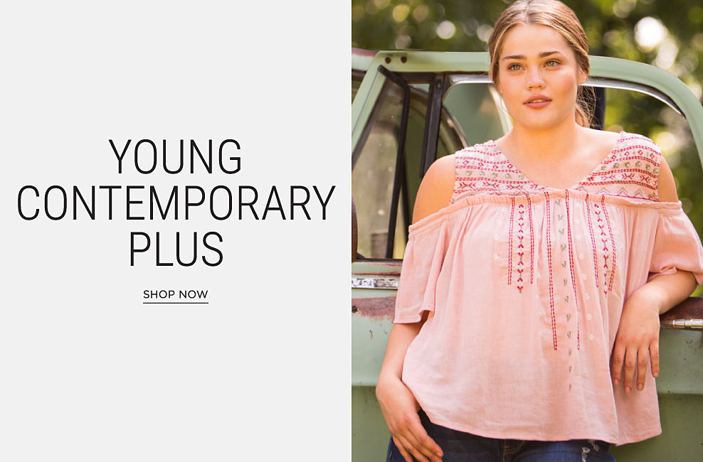 A young women wearing a peach & pink cold-shoulder top & blue jeans. Young contemporary plus. Shop now.