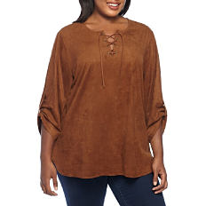 A woman wearing a brown long sleeved shirt with lace up neckline detail & blue jeans. Shop tops.