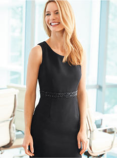 A woman wearing a black dress. Shop dresses.