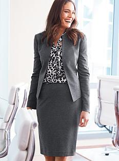 A woman wearing a gray blazer, a black & white print blouse & a gray skirt. Shop suits.