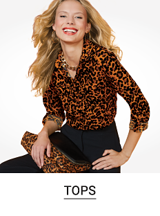 A woman in a leopard print button front top and black pants. Shop tops.