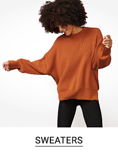 A woman in a dark orange sweater and black pants. Shop sweaters.