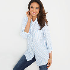 A woman wearing a white & light blue vertical striped long sleeved button front blouse & blue jeans. Shop tops.