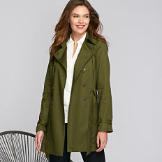 A woman wearing an olive green overcoat, a white top & blue jeans. Shop coats.