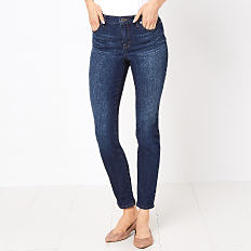 A woman wearing a white top, blue jeans and beige flats. Shop jeans.