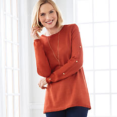 A woman wearing a red sweater, a white top & navy pants. Shop sweaters.