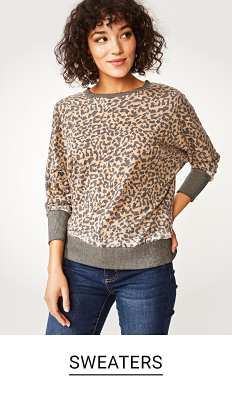 A young woman in a leopard print sweater and jeans. Shop sweaters.