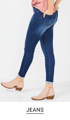 A young woman in a light pink top, jeans and light pink boots. Shop jeans.