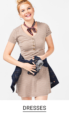 A young woman in a light brown and white stripe dress with a denim jacket wrapped around her waist. Shop dresses.