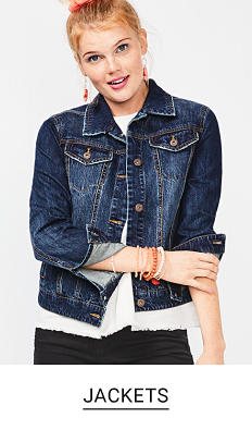 A woman in a white top, denim jacket and black pants. Shop jackets.