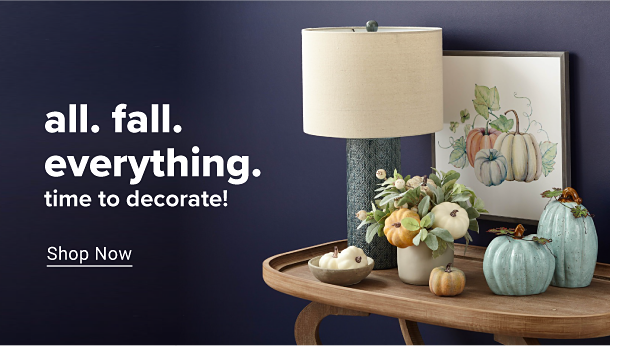 On a wooden table sit various pieces of fall decor, including small blue, orange and white pumpkins and a lamp. All fall everything. Time to decorate. Shop now.