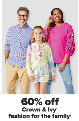 A man in a blue pullover and khaki pants. A little girl in a fall themed set with pumpkins and leaves. A woman in a warmed hued colorblocked sweater and distressed jeans. 60% off fashion for the family.