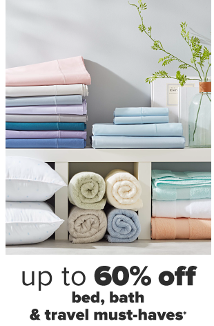 A home setting featuring folded towels and sheets in various shades and two pillows. Up to 65% off bed, bath and travel must-haves.