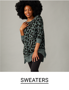Woman in a pale green sweater with large leopard print. Shop sweaters.