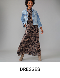Woman in a long black multi-colored floral dress with denim jacket. Shop dresses.