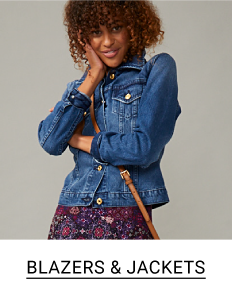 Woman in a purple dress with denim jacket. Shop blazers and jackets.