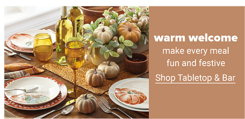 A harvest-themed tablescape featuring fall colors and decor. Atop the table are yellow-tinted wine glasses, orange dinner plates, white salad plates with a pumpkin design, plaid fabric napkins, a harvest-themed centerpiece and more. Warm welcome. Make every meal fun and festive. Shop tabletop and bar.