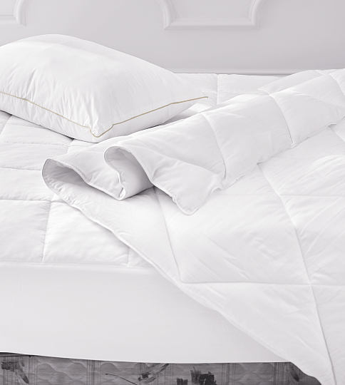 A bed made with a white comforter, pillow & sheets. Shop bedding essentials.