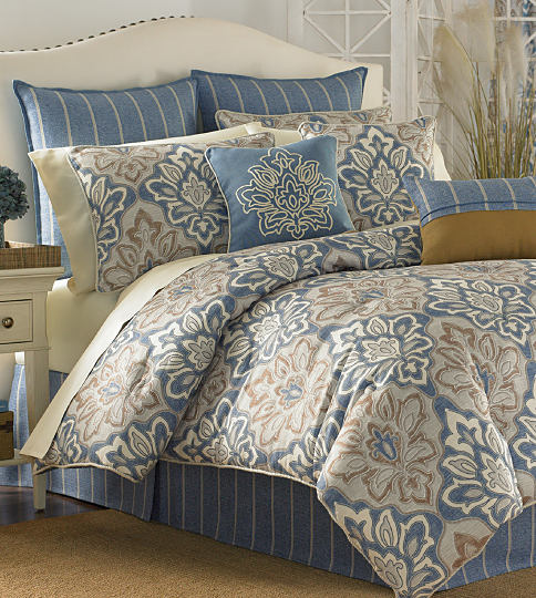 A bed made with a blue & beige patterned comforter & matching pillows. Shop bedding collections.