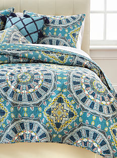A bed made with a multi-colored patterned quilt & matching pillows. Shop quilts.
