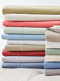 3 stacks of folded bed sheets in a variety of colors. Shop sheets.