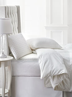 A bed made with a white comforter, matching cooling pillows & sheets. Shop Sleep Cool.