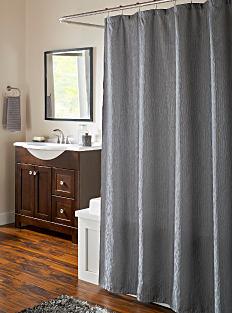 A dark gray shower curtain hanging over a white bath tub. Shop shower curtains.