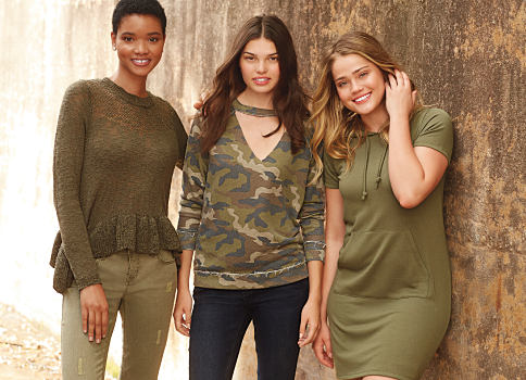 A woman wearing an olive green sweater & olive green pants standing next to a woman wearing a long-sleeved V-neck camo sweater & blue jeans. Shop sweaters